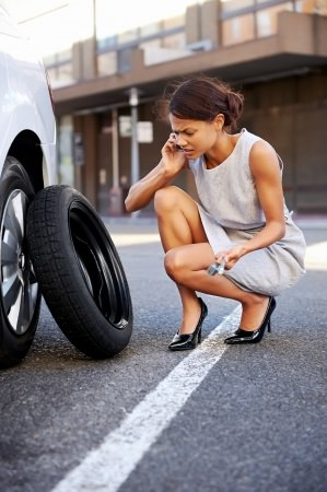 タイヤの修理ができずロードサービスに電話する女性
