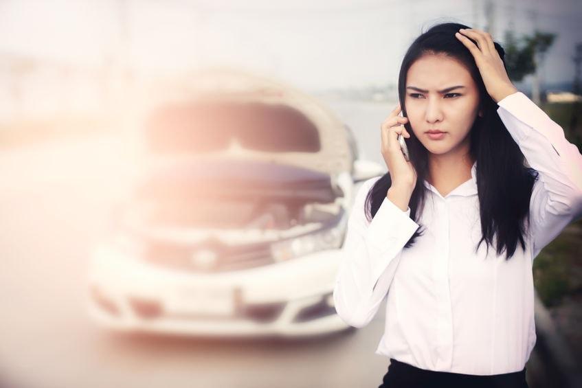 車故障後にロードサービスに電話する女性