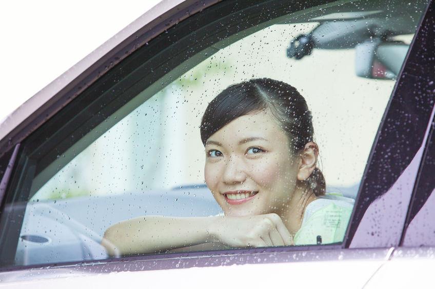 車の中から雨を眺める女性